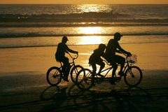 Family activities. Parents and a child riding bikes on the beach at sunset Stock Photo
