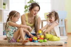 Family activities in the children room. Mother and her kids sitting on the foor playing. Family activities in the children room. Mother and her kids daughters royalty free stock image