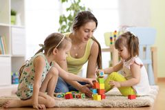 Family activities in the children room. Mother and her kids sitting on the foor playing. Family activities in the children room. Mother and her kids daughters stock photos