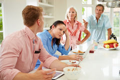 Family With Adult Children Having Argument At Breakfast. In Kitchen Looking At Each Other stock photography