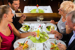 Family with adult kids in Restaurant. Family, mother and father with adult children and daughter or son in law –fine dining in nice restaurant or hotel stock image