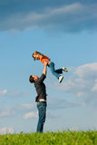 Family affairs - father and daughter. Father and his kid - daughter - playing together at a meadow, he is throwing her into the air at a late summer afternoon Royalty Free Stock Photography