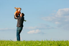 Family affairs - father and daughter. Father and his kid - daughter - playing together at a meadow, he is throwing her into the air at a late summer afternoon Royalty Free Stock Images