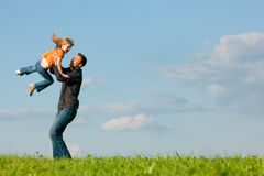 Family affairs - father and daughter. Father and his kid - daughter - playing together at a meadow, he is throwing her into the air at a late summer afternoon Stock Images