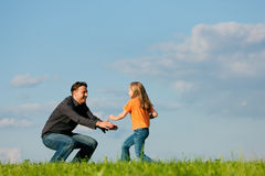 Family affairs - father and daughter. Father and his kid - daughter - playing together at a meadow, at a late summer afternoon, family concept Stock Images