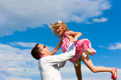 Family affairs - father and daughter playing in su. Mmer; he is throwing her into the air Stock Images