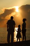Family against glossing sea. Parents and daughter Royalty Free Stock Photos