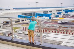 Family at airport before flight. Boy waiting to board at departure gate of modern international terminal. Traveling and royalty free stock image