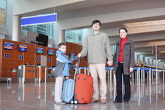 Family in airport hall with suitcases full bod Royalty Free Stock Image