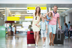 Family in the airport. Happy family with suitcases in the airport stock photo