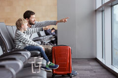 Family in airport. Positive smiling boy and his father waiting at the airport for plane departure and pointing with fingers at something, vacation and travel Royalty Free Stock Photos