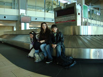 Family at Airport Stranded. Single mother and her two children at airport sitting on luggage carousel, waiting to get their lost luggage Royalty Free Stock Image