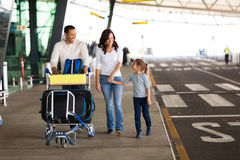 Family airport trolley. Cheerful young family at airport with a trolley full of luggage Royalty Free Stock Image