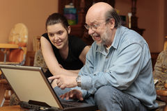 Family album on granddad's laptop. Enthusiast cheering bald granddad or grandfather showing and pointing family family photo album to smiling interested Stock Photos