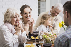 Family is all we have... Happy family sitting beside table during dinner, granddaughter sitting on grandfather's lap Royalty Free Stock Photography