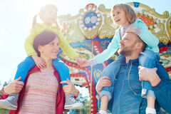 Family in amusement park. Cute girls and their parents visiting amusement park Royalty Free Stock Image