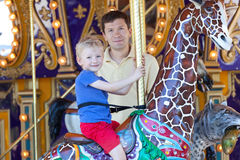 Family at amusement park. Happy smiling son and his handsome father spending fun time together at amusement park riding merry-go-round Stock Photo