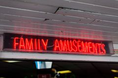 Family amusements sign on the street. Leisure concept with neon lights sign. Advertisement with neon lights on the street. Amuseme stock photography