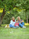 Family with apples and book in park Stock Photos