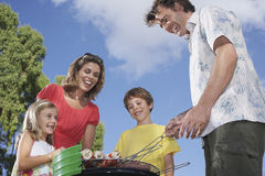 Family Around Grill In Garden Royalty Free Stock Photo