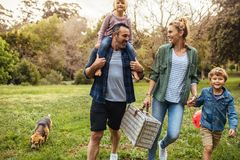 Family arriving in the park for picnic. Happy family with dog walking towards the picnic spot in the garden. Man carrying his daughter on shoulders with women royalty free stock photo