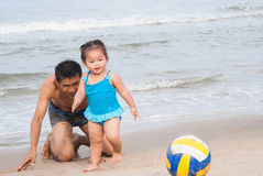 Family.Asian baby girl and father playing football on the beach. Stock Photography