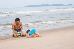 Family.Asian baby girl and father playing football on the beach. Royalty Free Stock Photos