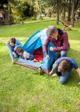 Family Assembling Tent At Campsite. Family of four assembling tent at campsite Stock Images