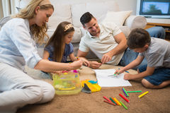 Family assisting boy in drawing Stock Images