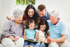 Family assisting girls while reading book. At home Royalty Free Stock Photo