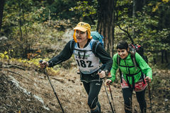 Family athletes climb uphill on forest trail Stock Photos