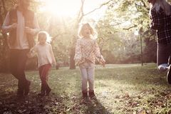 Family in autumn day. Little girl playing with rope royalty free stock image
