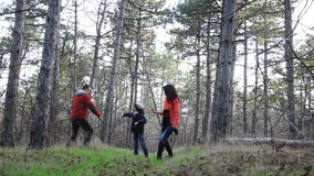 Family in autumn forest. Walk a happy family from three persons. Walk all family, among the trees in autumn forest stock footage