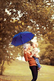 Family in autumn! Happy mother and child with umbrella Stock Image