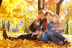 Family on autumn leaves Royalty Free Stock Photography