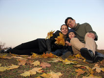 Family with autumn leaves. Sundown Royalty Free Stock Images
