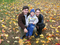 Family on autumn leaves. Smile family on autumn leaves royalty free stock photography