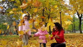 Family in autumn park throws up leaves. Mom and two daughters play with leaves in the park in the fall. Beautiful yellow stock video