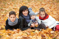 Family in autumn park on yellow leaves Stock Photo