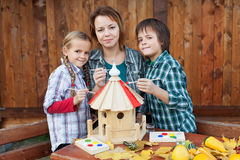 Family in autumn time preparing a bird house Royalty Free Stock Image