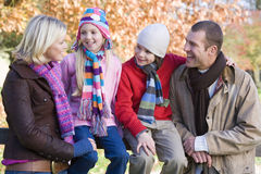 Family on autumn walk. Sitting on fence Stock Photography