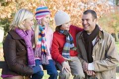 Family on autumn walk. Sitting on fence Stock Image