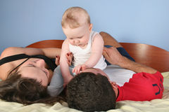 Family with baby on bed Stock Photos