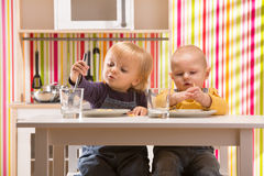Family baby brother and sister play eat meal in toy kitchen Royalty Free Stock Image