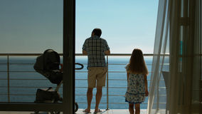 Family with baby carriage standing on the balcony Royalty Free Stock Photography