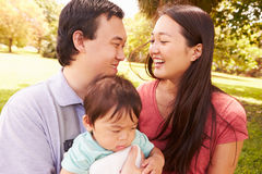 Family With Baby In Carrier Walking Through Park Stock Photography