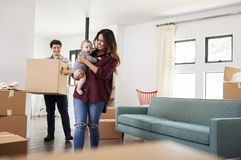 Family With Baby Carrying Boxes Into New Home On Moving Day royalty free stock images