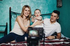 Family with baby daughter recording video for blog stock photography
