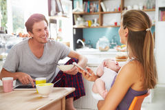 Family With Baby Girl Use Digital Devices At Breakfast Table Royalty Free Stock Photos
