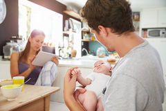 Family With Baby Girl Use Digital Tablet At Breakfast Table Stock Photography